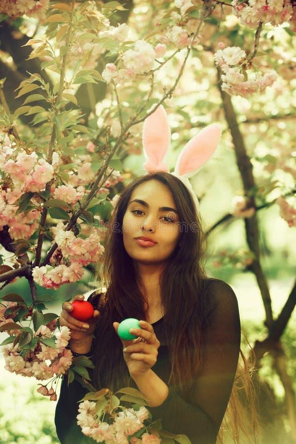 Fille avec des oreilles de lapin souriant avec les oeufs colorés, Sakura photographie stock libre de droits