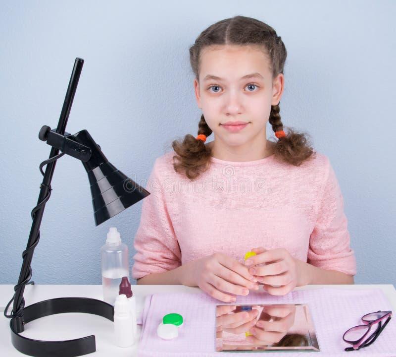 fille avec deux tresses, se reposant à la table et tenant un conteneur pour stocker des verres de contact image stock