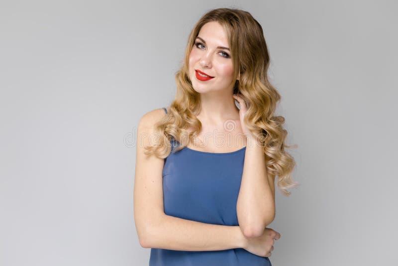 Fille avec du charme avec de longs cheveux bouclés blancs Fille dans un dessus bleu sur un fond clair photo libre de droits