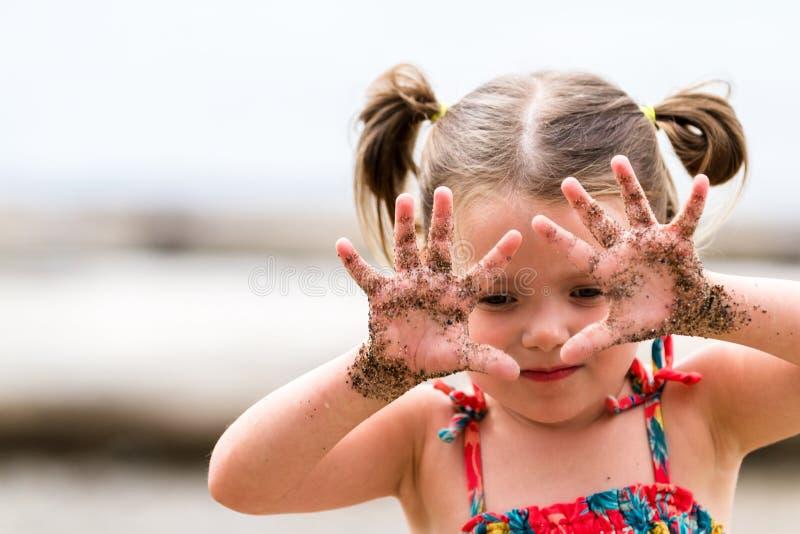 Fille avec du sable sur les mains image stock