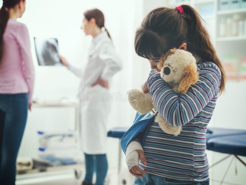 Fille avec l'accolade de bras dans le bureau du docteur images stock