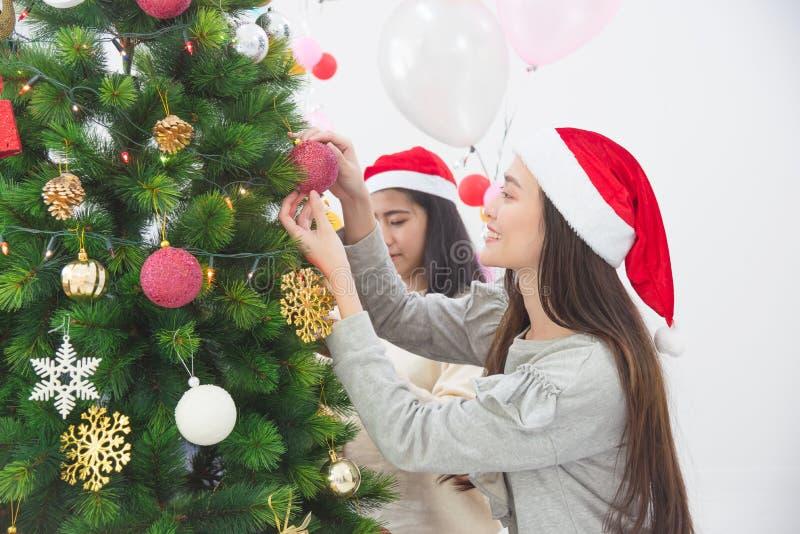 Fille avec l'ami décorant l'arbre de Noël à la maison photos stock