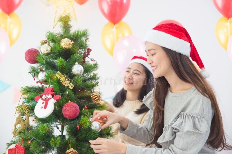Fille avec l'ami décorant l'arbre de Noël à la maison photo stock