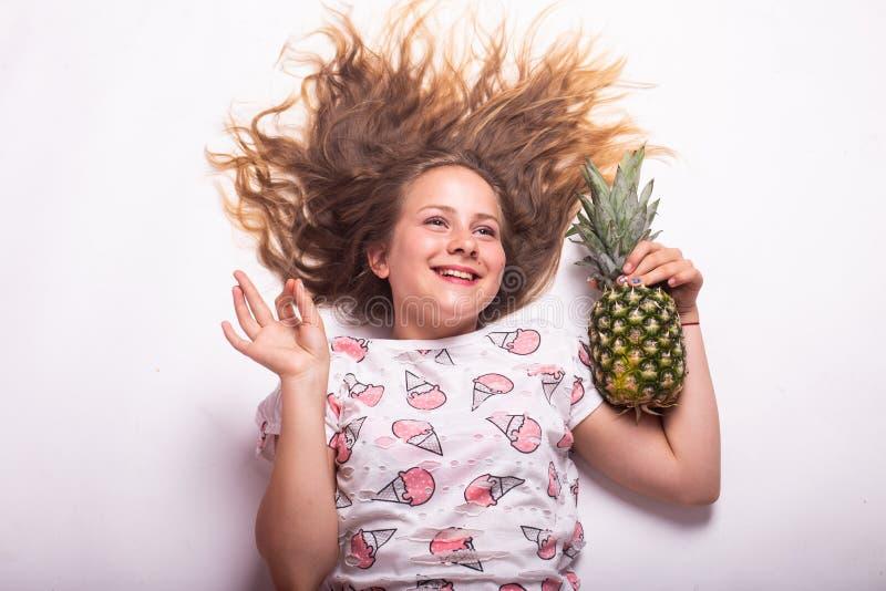 Fille avec l'ananas sur le fond blanc image libre de droits