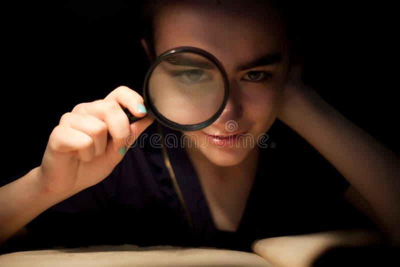 Fille avec l'oeil avant en verre de magnifir photos libres de droits
