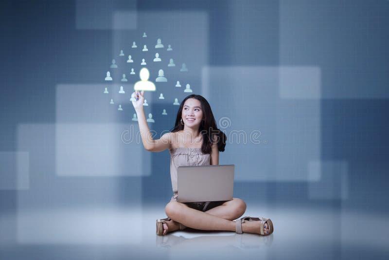 Fille avec l'ordinateur portable et l'icône sociale de réseau photo libre de droits