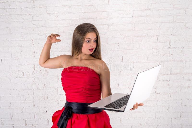 Fille avec l'ordinateur portable sur le fond de mur de briques photographie stock libre de droits