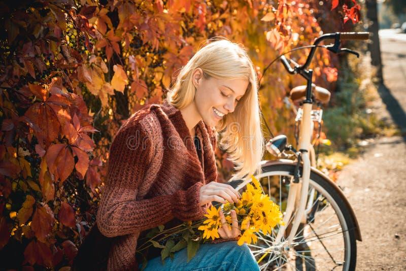 Fille avec la bicyclette et les fleurs Jardin d'automne de bicyclette de femme Loisirs et mode de vie actifs Plaisirs simples d'a photographie stock libre de droits