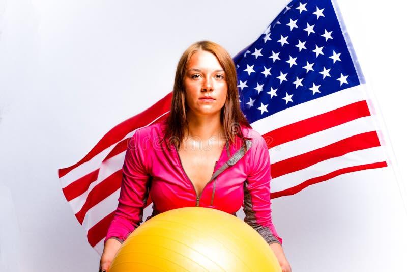 Fille avec la boule et le drapeau américain photo stock