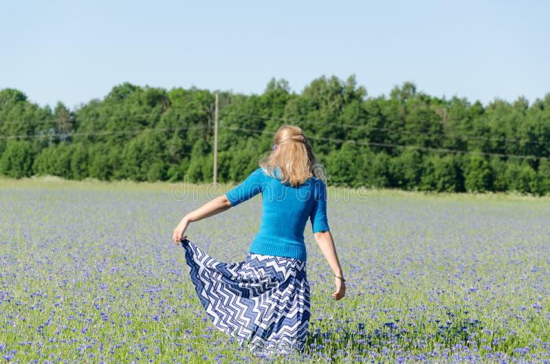 Fille avec la danse bleue de jupe dans le pré de bleuet photos libres de droits