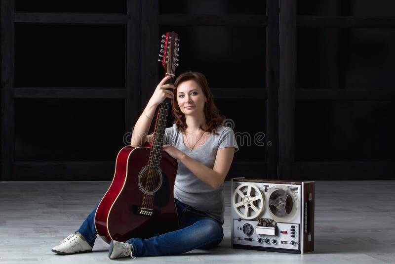 Fille avec la guitare et la bande photos stock