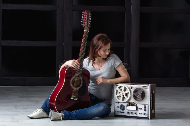 Fille avec la guitare et la bande image stock
