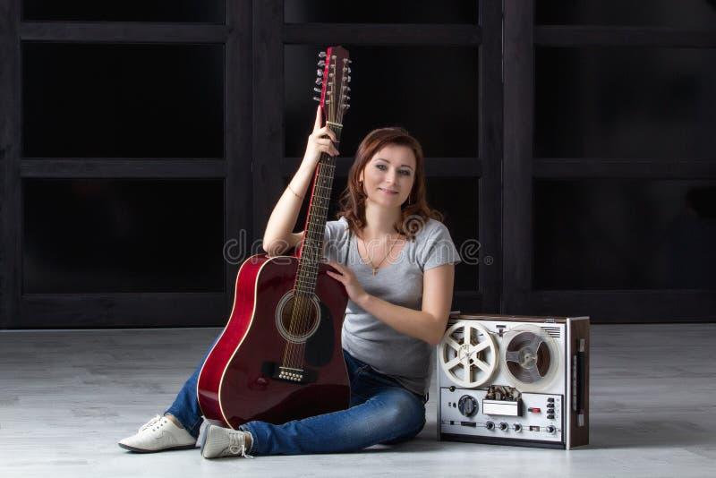 Fille avec la guitare et la bande photographie stock