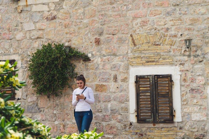 Fille avec la longue chemise blanche envoyant un message dans le téléphone intelligent et la maison en pierre avec des fleurs dan photographie stock libre de droits