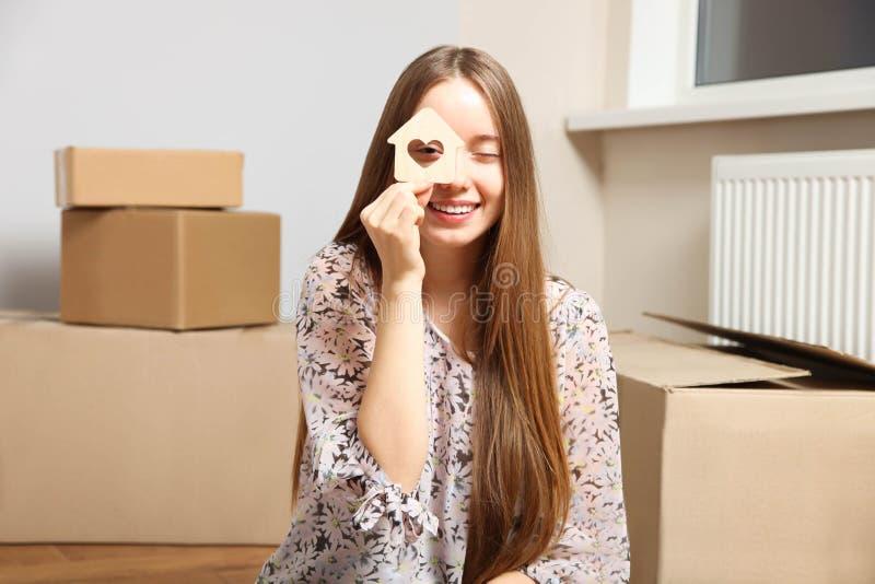 Fille avec la maison en bois à disposition sur le fond des boîtes en carton photos libres de droits