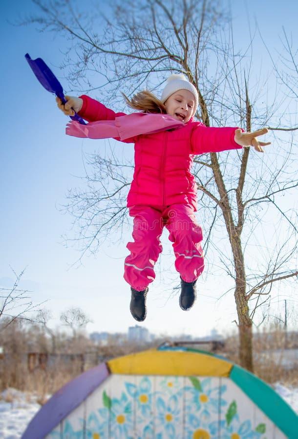 Fille avec la pelle sautant en hiver photographie stock
