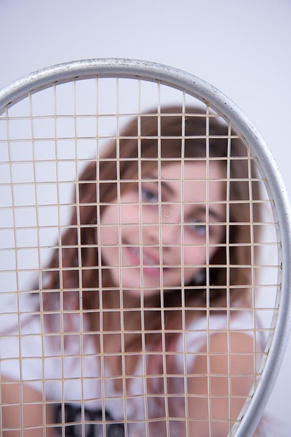 Fille avec la raquette de tennis dans votre visage image stock