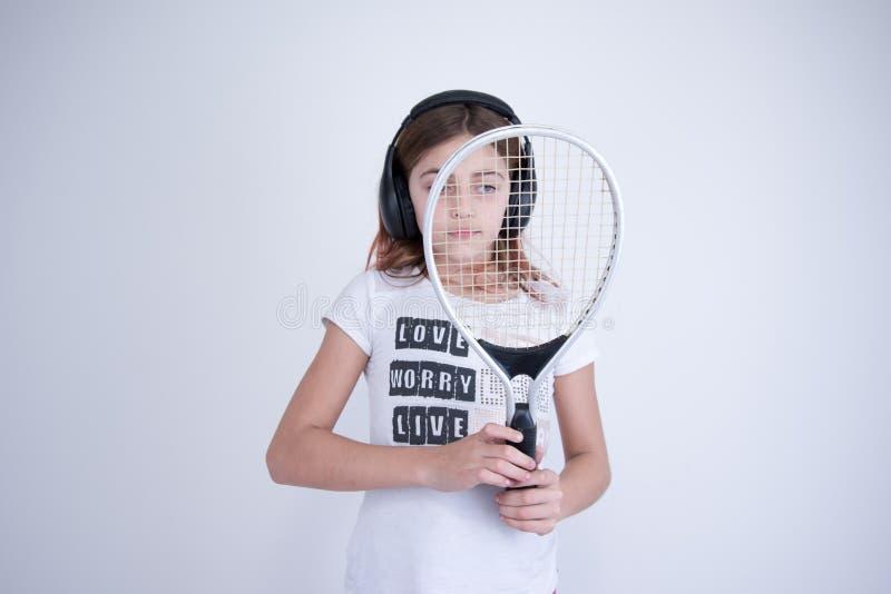 Fille avec la raquette de tennis semblant droite photos stock