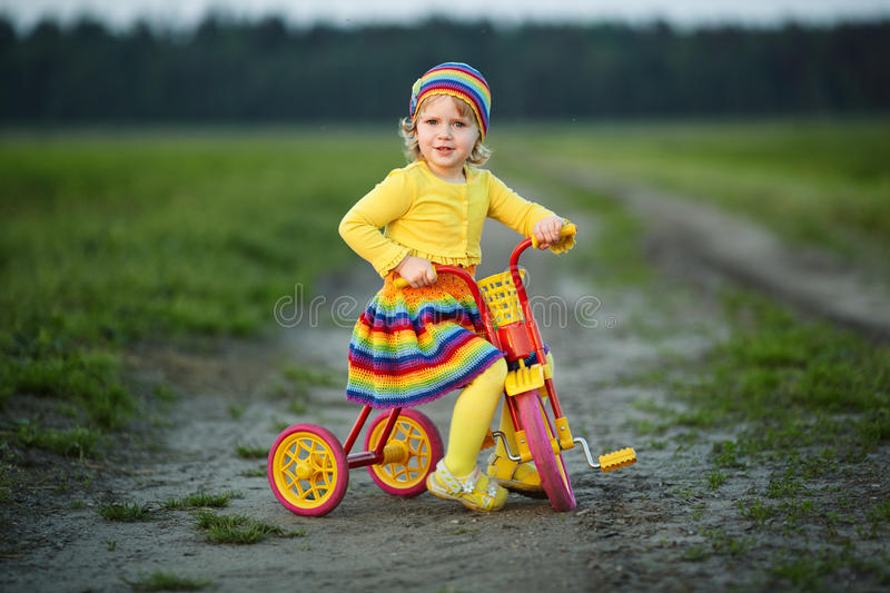 Fille avec la robe colorée sur la bicyclette photo stock