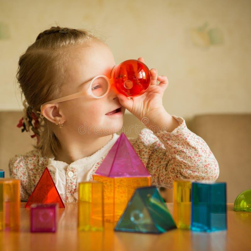 Fille avec la trisomie 21 jouant avec des formes géométriques photo stock