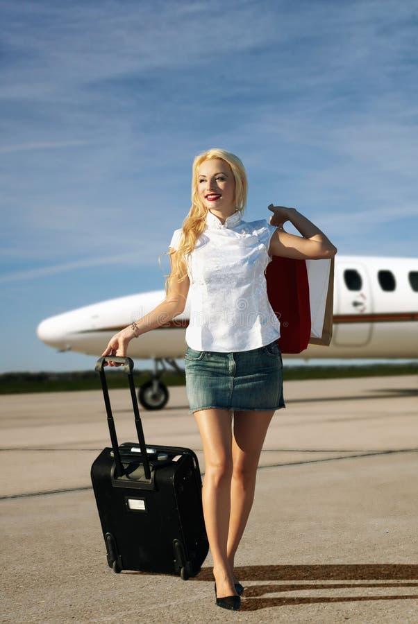 Fille avec le bagage allant de l'avion photos stock
