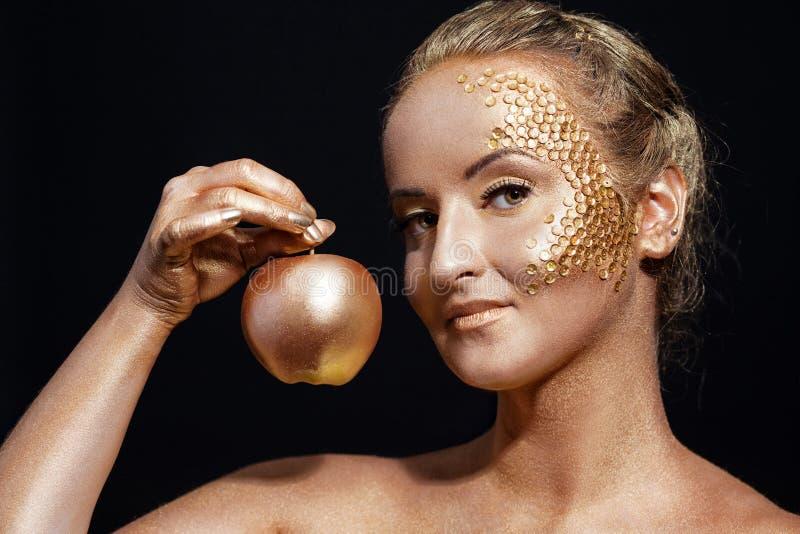 Fille avec le bodyart d'or posant avec la pomme d'or photographie stock