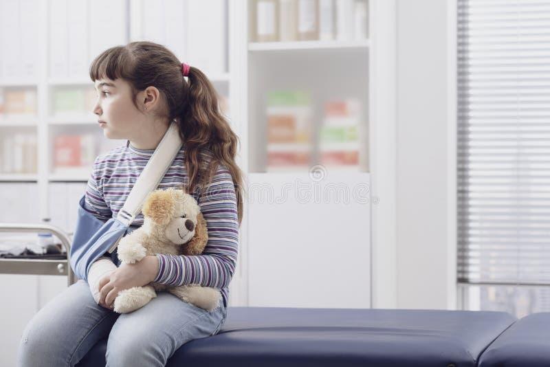 Fille avec le bras cassé attendant dans le bureau du docteur photo stock