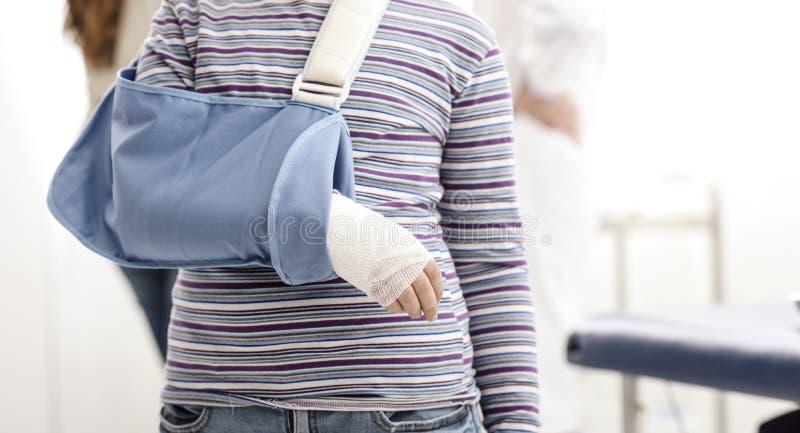 Fille avec le bras cassé et accolade de bras dans le bureau du docteur photos libres de droits