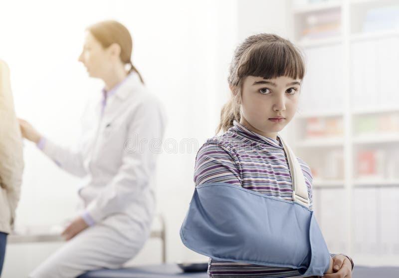 Fille avec le bras cassé et accolade de bras dans le bureau du docteur image libre de droits