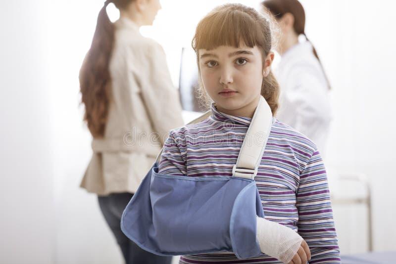 Fille avec le bras cassé et accolade de bras dans le bureau du docteur images libres de droits