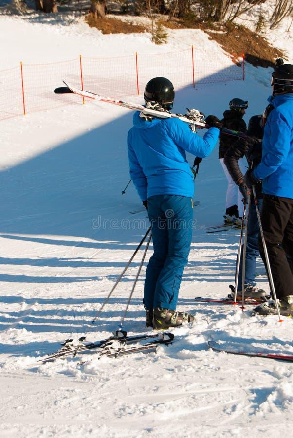 Fille avec le casque et ski sur l'épaule après le ski dans un jour ensoleillé photographie stock