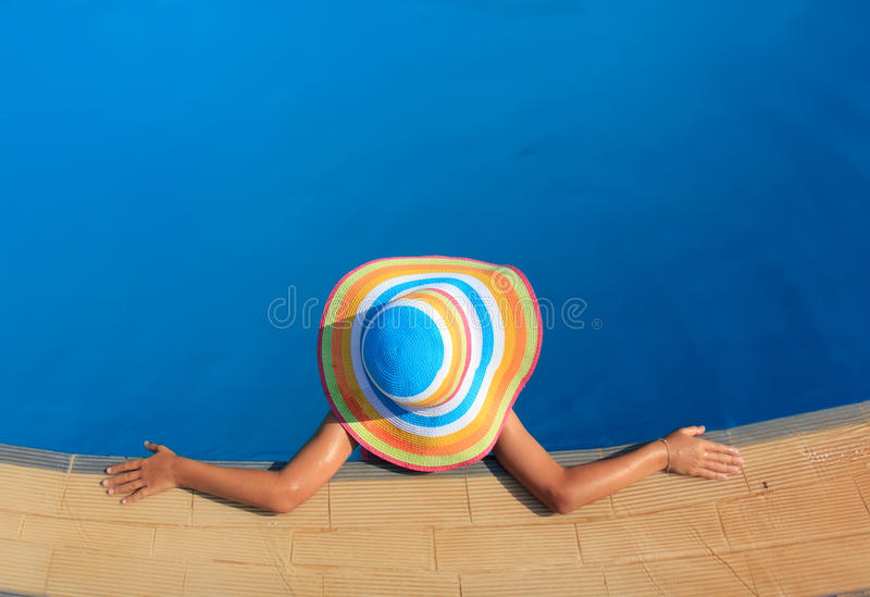 Fille avec le chapeau coloré dans la piscine image stock