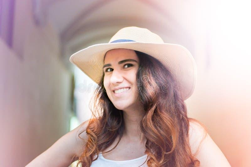 Fille avec le chapeau le jour d'été dans la rue photographie stock libre de droits