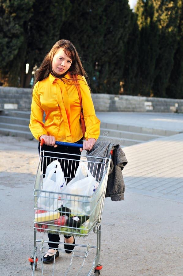 Fille avec le chariot à achats photos stock