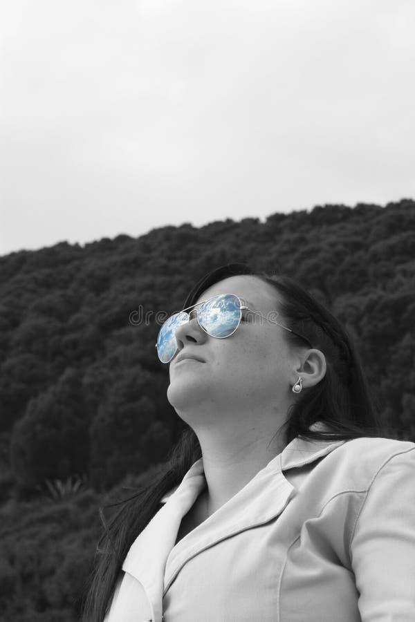 Fille avec le ciel dans des lunettes de soleil images libres de droits