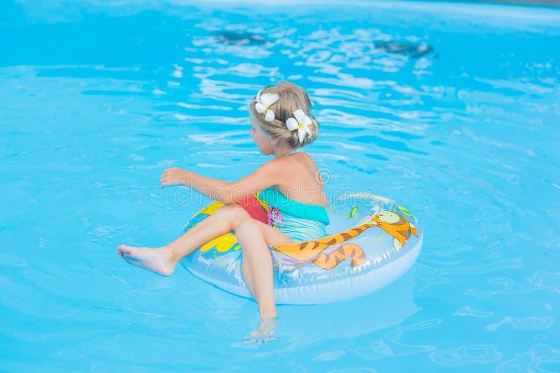 Fille avec le frangipani de fleurs sur sa tête dans ses cheveux flottant sur le cercle dans la piscine un jour ensoleillé image libre de droits