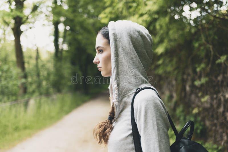Fille avec le hoodie marchant dans les bois photo stock
