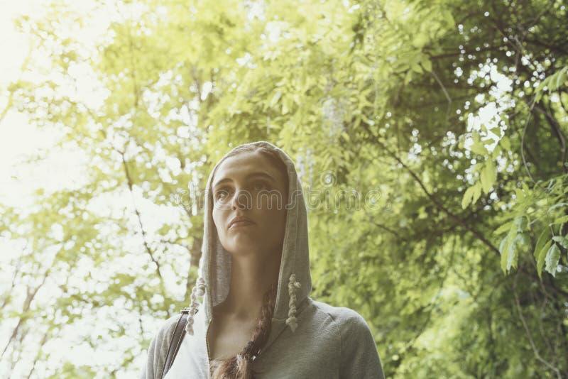 Fille avec le hoodie marchant dans les bois photographie stock