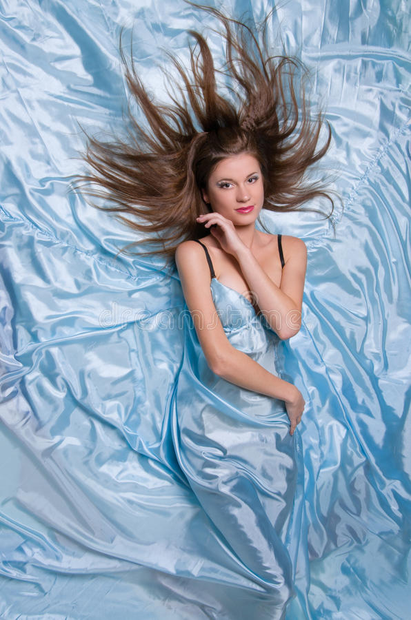 Fille avec le long cheveu se trouvant sur les tissus en soie bleus photos libres de droits