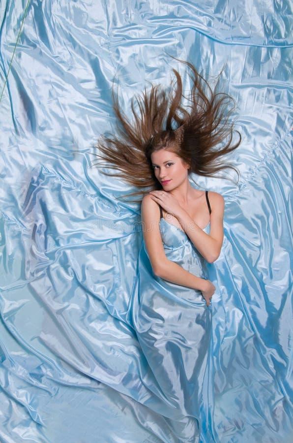 Fille avec le long cheveu se trouvant sur les tissus en soie bleus image stock