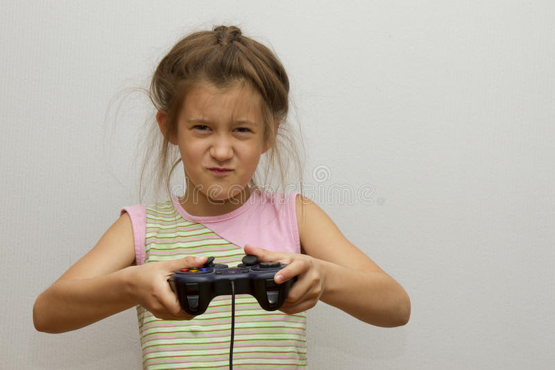 Fille avec le manche Petite fille enthousiaste jouant le jeu vidéo et le sourire image libre de droits