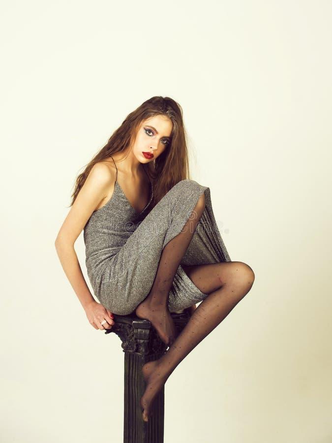 fille avec le maquillage à la mode de scintillement dans la robe, collants sur la colonne photographie stock