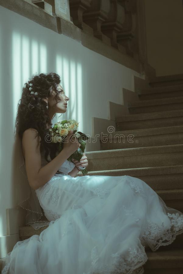Fille avec le maquillage et la coiffure nuptiales Femme sensuelle avec le bouquet de mariage La femme avec des fleurs s'asseyent  photographie stock