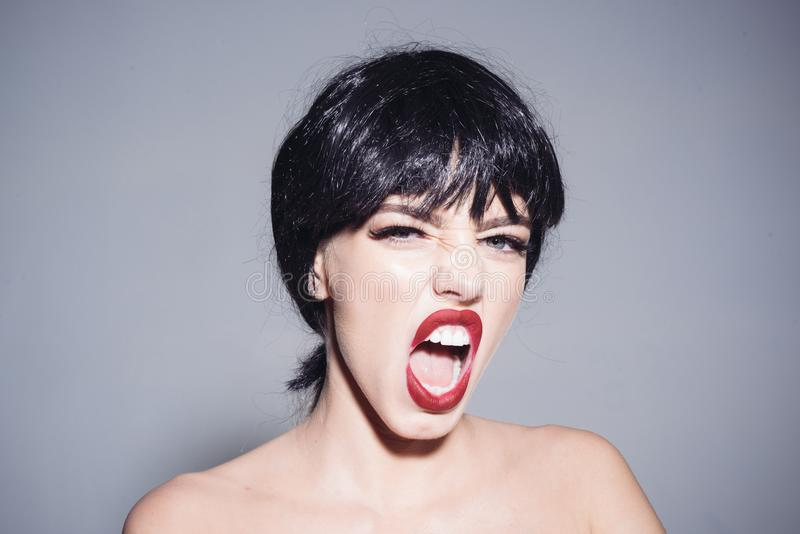 Fille avec le maquillage rouge de lèvres portant la perruque noire d'isolement sur le fond gris Femme avec le visage fâché hurlan image stock
