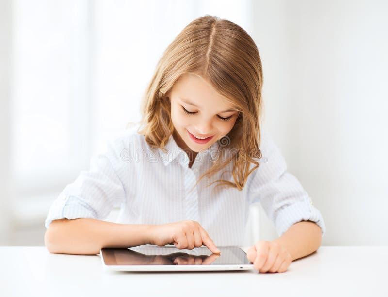 Fille avec le PC de comprimé à l'école image stock