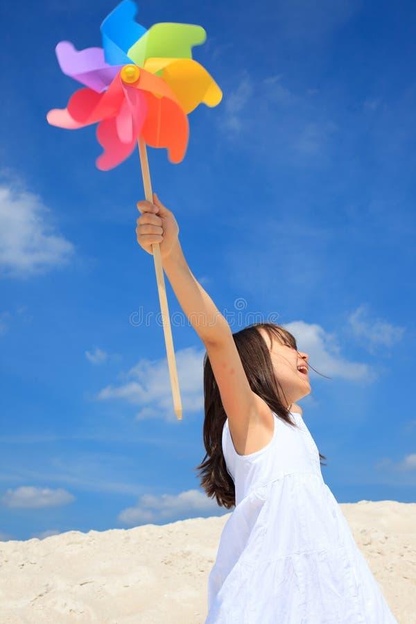 Fille avec le pinwheel sur la plage photographie stock libre de droits