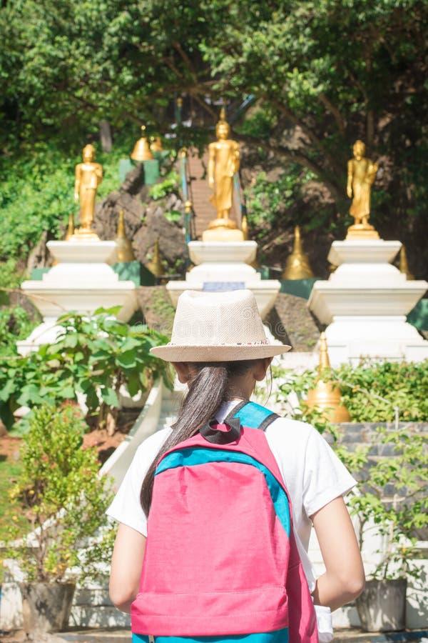 Fille avec le sac à dos entrant au temple bouddhiste, Thaïlande photo libre de droits