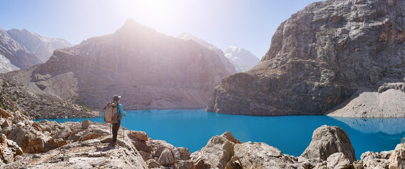 Fille avec le sac à dos près du lac grand Alo sur le backgroun de montagne rocheuse images libres de droits