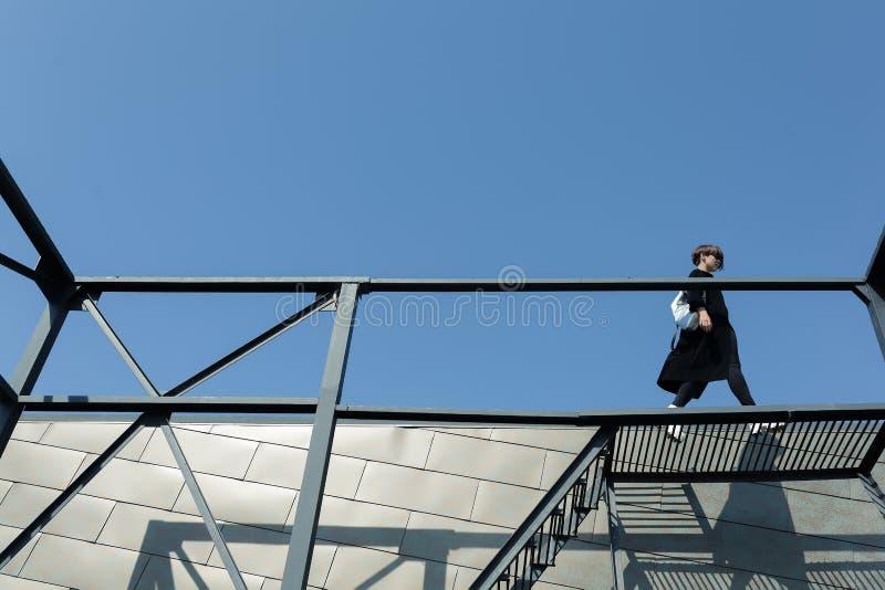 Fille avec le sac blanc sur les escaliers photographie stock libre de droits