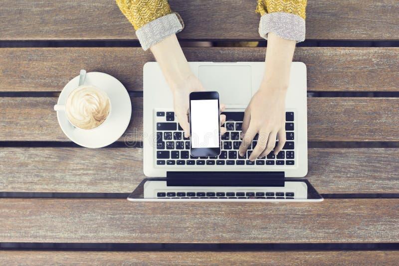 Fille avec le smartphone, l'ordinateur portable et le cappuccino vides sur le tabl en bois photos stock